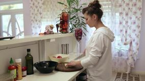 Young beautiful woman preparing a salad in the kitchen. Tomatoes and bell peppers. stock footage