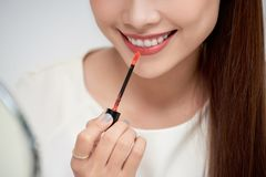 Young beautiful woman professional beauty vlogger or blogger applying lipstick cream to her mouth, doing a make up tutorial stock photos