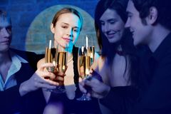 Young beautiful woman in projector beam, celebrating with friends Royalty Free Stock Image