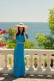 Young beautiful woman on the promenade in azure long dress takes Royalty Free Stock Photo