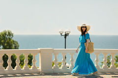 Young beautiful woman on the promenade on the sea in azure long Royalty Free Stock Photo