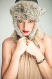Young beautiful woman pulling her fur hat on Royalty Free Stock Photography
