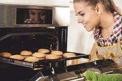 Young beautiful woman pulls cookies from the oven.  royalty free stock photo