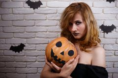 Young beautiful woman with pumpkin in hands posing at camera. Ha. Young beautiful woman with pumpkin in hands and creepy makeup posing at camera. Halloween royalty free stock photography