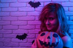 Young beautiful woman with pumpkin in hands posing at camera. Fr. Ee space for text design. Halloween, celebration, party concept royalty free stock photos