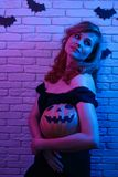 Young beautiful woman with pumpkin in hands posing at camera par. Tying in a nightclub. Halloween, celebration, party concept stock photo