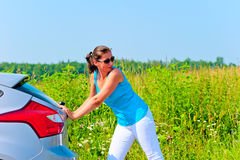 Young beautiful woman is pushing broken car on the road Stock Photo