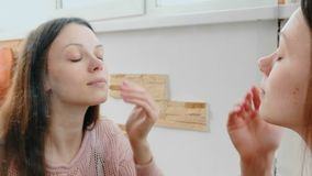 Young beautiful woman puts a cream on her face in front of the mirror. Front view. Young beautiful woman puts a cream on her face in front of the mirror. Front stock video