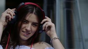 Young and beautiful woman is putting on big headphones dancing stock video footage