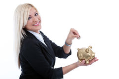 Young beautiful woman putting a coin into a big  piggy bank. Young bussines woman putting a coin into a big  piggy bank Royalty Free Stock Photo