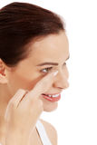 Young beautiful woman putting contact lens. Royalty Free Stock Photos