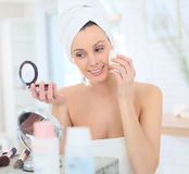 Young beautiful woman putting makeup on Stock Image