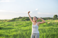 Young beautiful woman raised arms enjoying the fresh air in gree Stock Photo