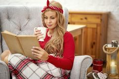 Young beautiful woman reading a book in an armchair with blanket and tea during Christmas time. Young beautiful woman sitting and reading a book and drinking tea stock photos