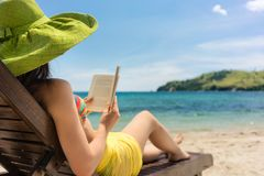 Young beautiful woman reading a book at the beach in a sunny day Royalty Free Stock Image