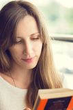 Young beautiful woman reading a book Stock Images