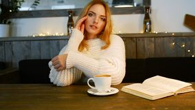 Young beautiful woman is reading a book in cafe. She is smiling and enjoying the aroma of coffee. stock footage