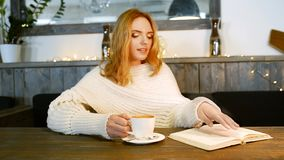 Young beautiful woman is reading a book in cafe. She is smiling and enjoying the aroma of coffee. stock video