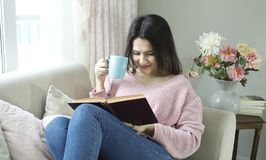 Young beautiful woman is reading book on couch and drinking coffee. stock photo
