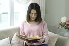 Young beautiful woman is reading a book on the couch. stock photos