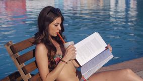 Young beautiful woman reading the book near the swimming pool stock footage