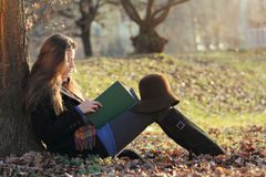 Young beautiful woman reading a book at the park Royalty Free Stock Image