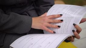A young beautiful woman reading the journal in a park by autumn. Close-up of hands and the pages of the magazine