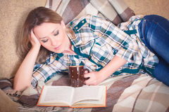 Young beautiful woman reading lying on a sofa Royalty Free Stock Images