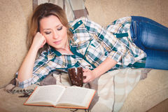 Young beautiful woman reading lying on a sofa Stock Image