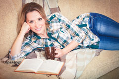 Young beautiful woman reading lying on a sofa Royalty Free Stock Image
