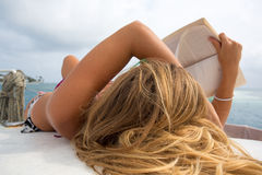 Young beautiful woman is reading and sunbathing Royalty Free Stock Image