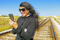Young beautiful woman is reading a text message on a railroad tr Royalty Free Stock Photo