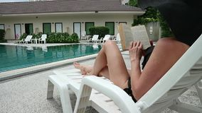 Young beautiful woman reads a book near the swimming pool. Slim girl sitting in chaise-longue stock video