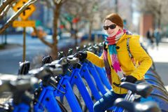 Young beautiful woman ready to rent a city bike Royalty Free Stock Photos