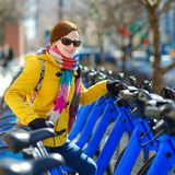 Young beautiful woman ready to rent a city bike. In New York, USA Stock Image