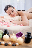 Young beautiful woman  received treatment with hot stones on her Stock Image