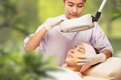Young beautiful woman receiving cosmetic facial mask in spa beauty salon stock photos