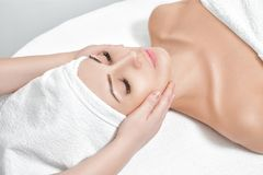 Woman receiving facial massage at spa salon. Young beautiful woman receiving facial massage at spa salon stock photo