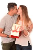 Young Beautiful Woman receiving Present and kissing handsome man. Young Beautiful Woman receiving Present and kissing handsome men isolated on white background Stock Images