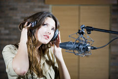 Young beautiful woman recording the sound. Young beautiful retro woman recording the sound in professional studio with mic and phones. indoor Royalty Free Stock Images
