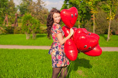 Young beautiful woman with red balloons walking outdoor Royalty Free Stock Image