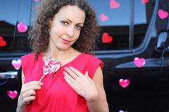 Young woman with candy heart stands near to offroader Stock Photography