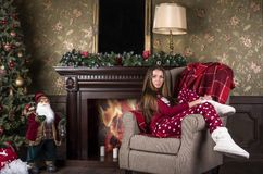 Young beautiful woman in red Christmas home clothes pajamas and white home boots sits in a chair against the background of th. E Christmas tree and fireplace stock image