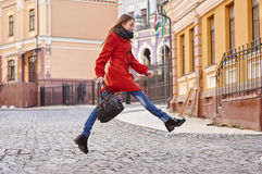 Young beautiful woman in red coat in the city Royalty Free Stock Photos