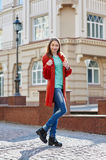 Young beautiful woman in red coat in the city Stock Images