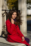 Young beautiful woman in red coat enjoying sun. Royalty Free Stock Images