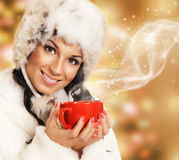 Young and beautiful woman with a red cup on a Christmas background. A young and beautiful woman with a red cup of coffee. The image is taken over abstract Royalty Free Stock Image