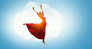 Dance is her passion. Young beautiful woman in red dress flying in air Royalty Free Stock Photo
