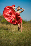 Young beautiful woman in red dress flying in wind Stock Images
