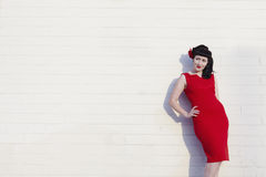 Young beautiful woman in red dress leaning on wall Stock Photo